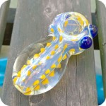 Incredibly thick color changing glass pipe with vertical rows of colorful dots leading to a flower pattern on the front of the bowl