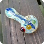 Silver fumed glass spoon pipe with blue dichroic strip down the center and green, yellow, and red dots along the right side of the bowl.