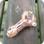 Glass smoking pipe with blue, orange, and white stripes on a silver fumed background with a clear glass bead on the right side