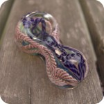 Peanut-shaped glass pipe with latticino inside out designs in various colors on a silver fumed, color changing background.