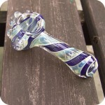 Silver fumed color changing glass pipe with swirls of color throughout the body, a clear raised carburetor, and clear orbs on the front.