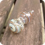 Hand blown, silver fumed, color changing glass pipe with colored stripes spiraled around its puffed out body and tapered mouthpiece