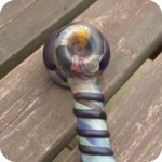 Hammer style glass bubbler featuring full-color jewel-toned glass and decorative elements on the outside